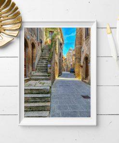 Plakat z malowniczą uliczką pod lazurowym niebem